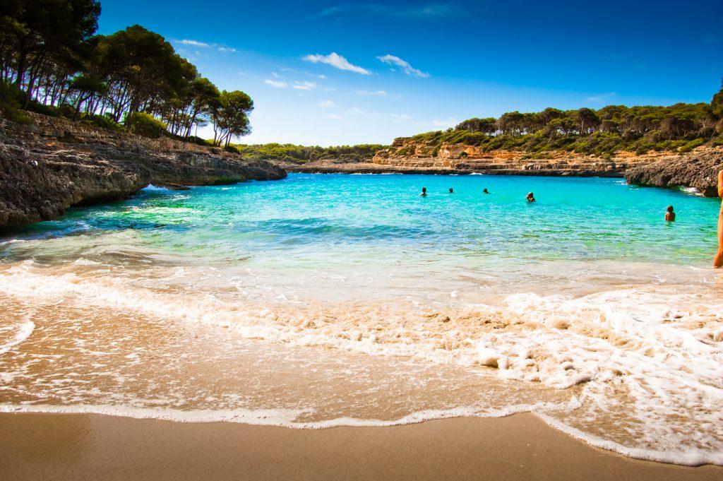 Mediterraner Strand umgeben von Palmen