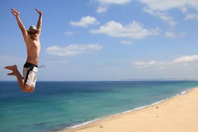 springender Urlauber am Strand