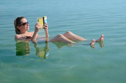 Frau liest Buch im toten Meer
